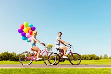 Gelukkige familie die de zomer weekend en fietsen