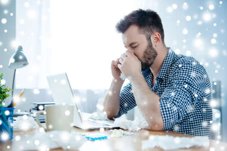 Sick businessman with fever and running nose  on winter background Stock Photo