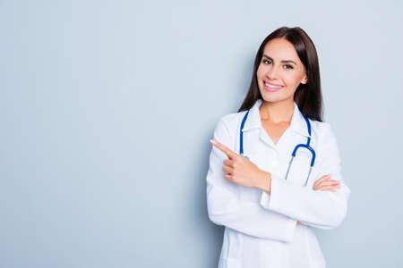Sorridente medico felice che punta con il dito su sfondo blu Archivio Fotografico