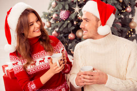 Portrait of happy couple in love drinking tea on xmas Stock Photo