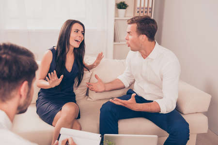 Portrait of young family quarreling at a reception of psychologist Stock Photo