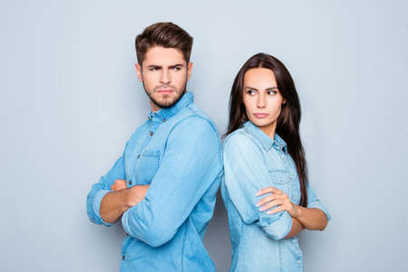 Serious man and woman with crossed hands standing back to back after quarrel