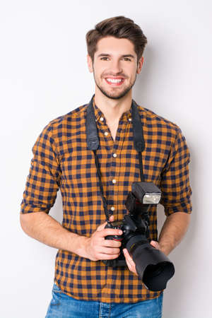 Portrait of young handsome cheerful photographer holding camera