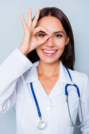 Smiling female doctor  in white coat  showing OK gesture near eye