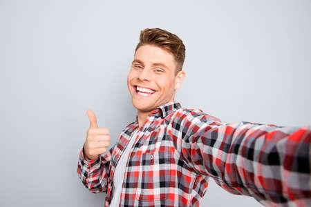 ハンサムな陽気な若い男 selfie と示す親指を作る