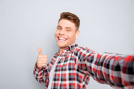 Handsome cheerful young man making selfie and showing thumb up