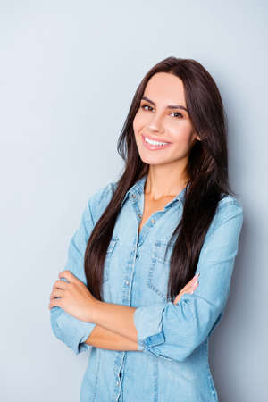 Portrait of attractive toothy woman in jeans shirt with crossed hands