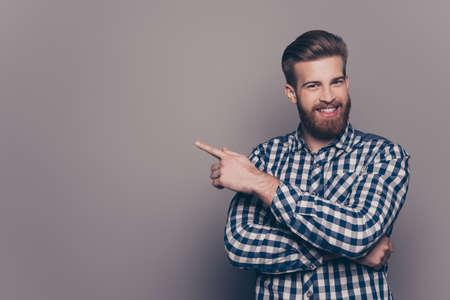 陽気なハンサムなスタイリッシュな男の方向を示し、指で指しています。