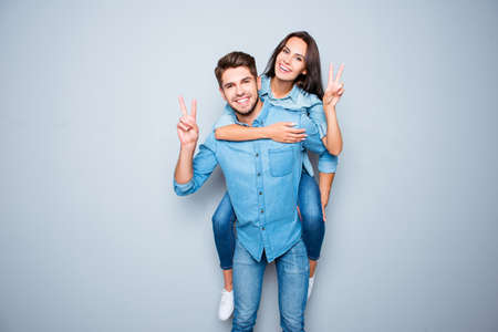 Smiling happy man piggybacking his girlfriend and gesturing v-sign