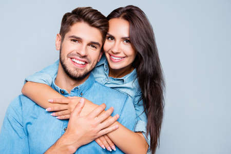 Portrait of happy cute lovers embracing on gray background Stock Photo