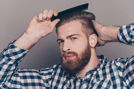 Portrait of handsome cheerful bearded young man combing his hair Stock Photo