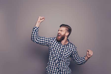 はい、彼はそれをやった!手と叫びの肖像スタイリッシュな幸せなひげを生やした男が発生しました。 写真素材