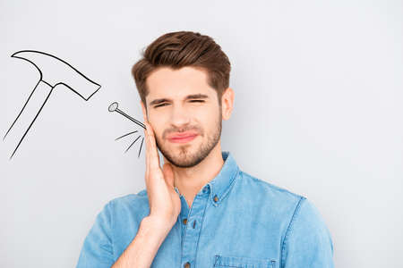 Sad man having toothache and touching cheek. Drawn  hammer near Stock Photo
