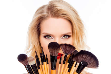 woman hiding: Portrait of young pretty woman hiding face behind makeup brushes