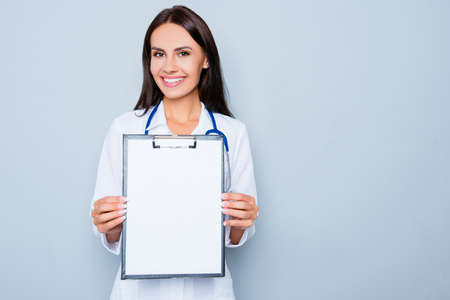 Young happy smiling doctor showing folder with diagnosis