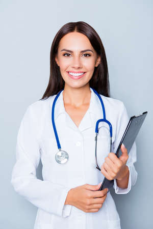 Happy young nurse holding folder isolated on lue background