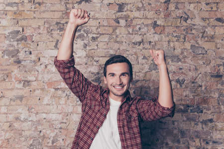 triumphing: Yes! Young happy man triumphing with raised fists