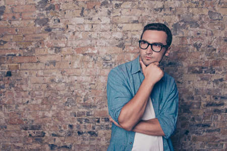 Portrait of minded man in glasses  on brick wall background