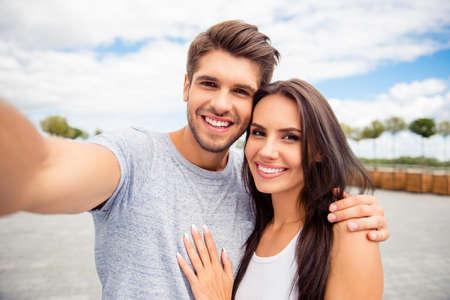 市内で selfie を取って明るく幸せなカップルを愛する 写真素材
