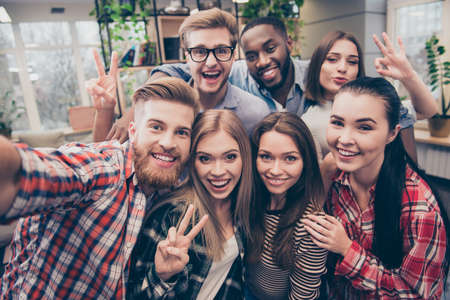 Young happy friends  gesturing v-sign while making selfie Stock Photo - 70951644