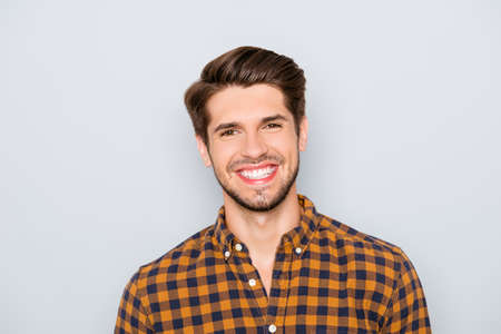 Portrait der schönen jungen Mann mit einem Lächeln auf grauem Hintergrund strahlend Standard-Bild