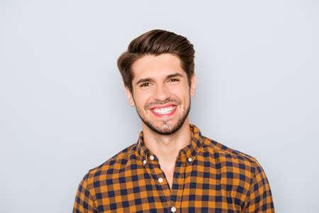 Portret van knappe jonge man met stralende glimlach op grijze achtergrond