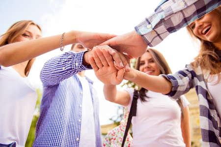 Sluit omhoog foto van jonge vrienden die hun handen bovenop elkaar zetten