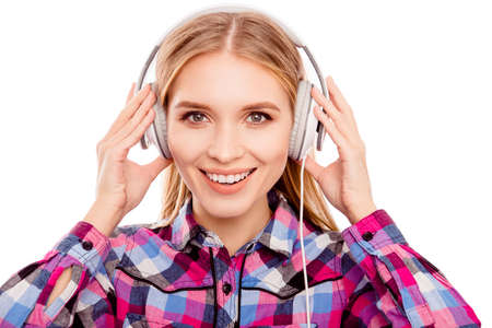 Happy young blonde woman listening music with headphones
