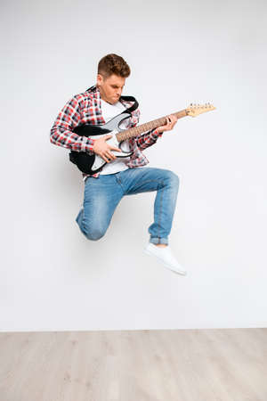 instrumentalist: Portrait of trendy rocker guy jumping with electric guitar