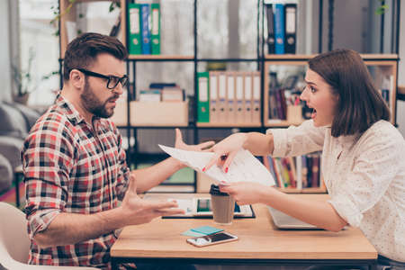 Young frustrated woman yelling and screaming on her colleague Stock Photo