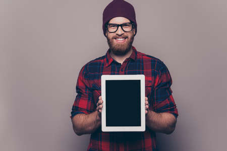 Happy young hipster man showing blank tablet screen