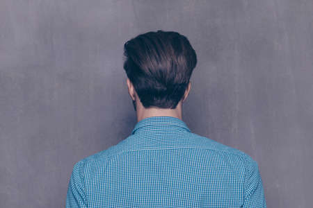 Back view of young guy in blue shirt  on gray background