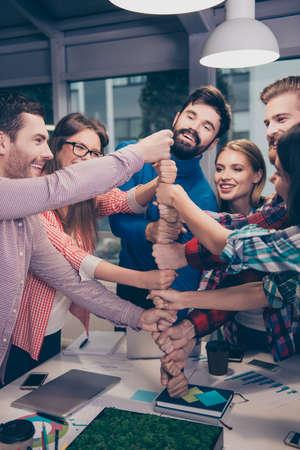 Gelukkig ondernemers zetten hun vuist op de top van elkaar en lachen