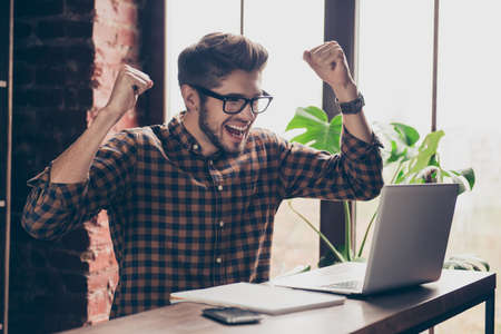 triumphing: Happy young bearded manager with laptop completing task and triumphing