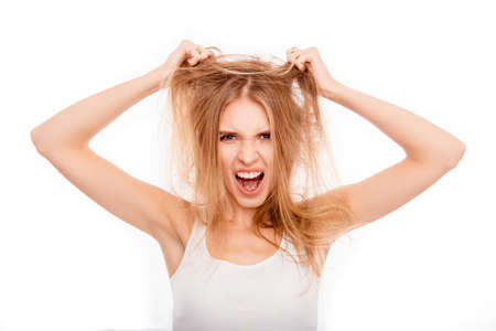 Frustrated young blonde holding her damaged hair and yelling