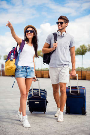 Young happy family having honeymoon and finding way to hotel from airport
