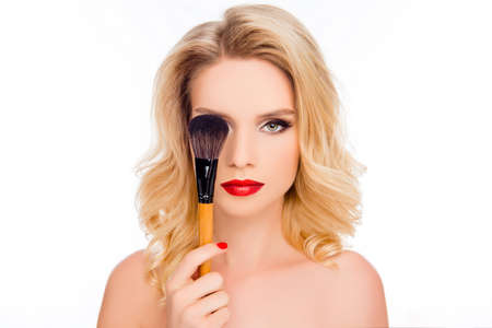 Portrait of pretty blonde with bright makeup hiding eye behind make-up brush