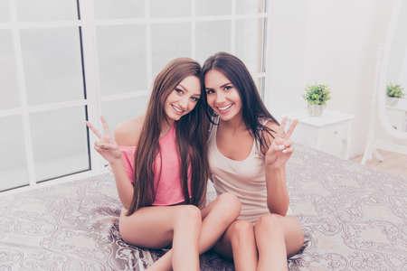 pijamada: Dos chicas muy sonrientes en pijama gesticulando signo v