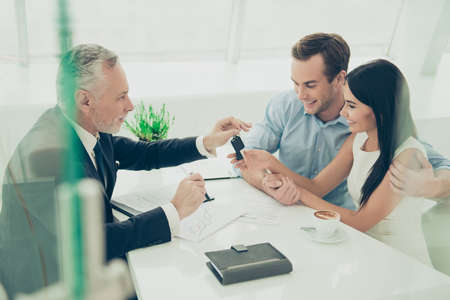 accommodation broker: Real estate agent working with couple of customers and giving them keys Stock Photo