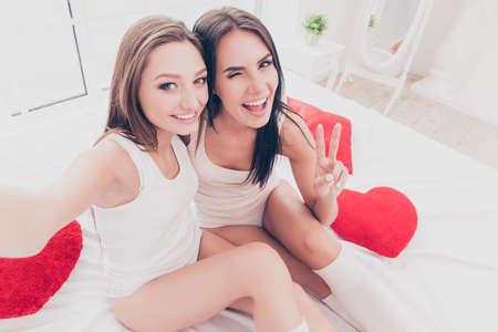 pijamada: Happy cheerful sisters making selfie in morning and gesturing v-sign Foto de archivo