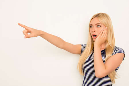 Shocked blonde touching her face and pointing away Stock Photo