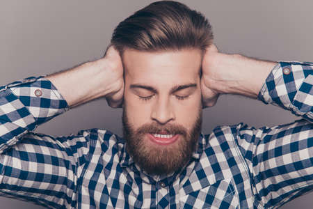 hands covering ears: Angry bearded man with closed eyes covering ears with hands