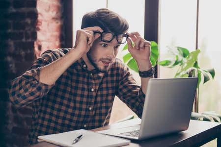 Unbeliveable! Jonge geschokte verraste mens die in glazen op laptop kijkt Stockfoto