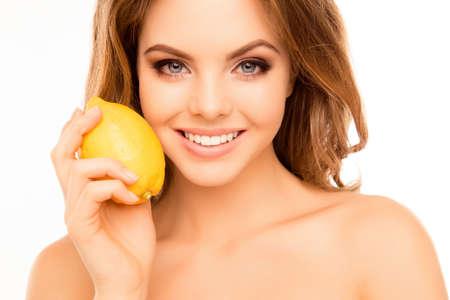 entice: Portrait of beautiful sensitive woman holding lemon near face Stock Photo