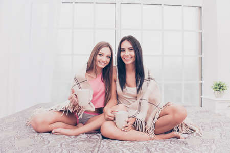 Two sisters sitting on bed and basking with plaid and coffee Stock Photo