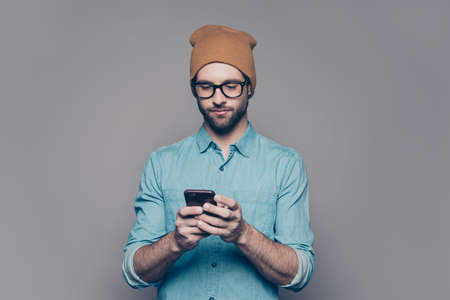 Handsome young man in yellow hat and glasses typing sms Фото со стока