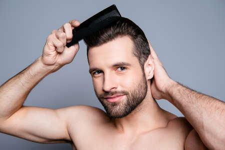 Portrait  of young handsome man combing his hair