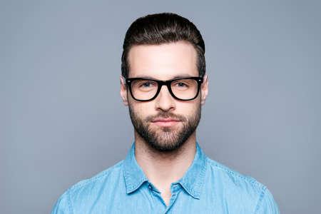 Ritratto di giovane uomo barbuto bello in vetri su sfondo grigio