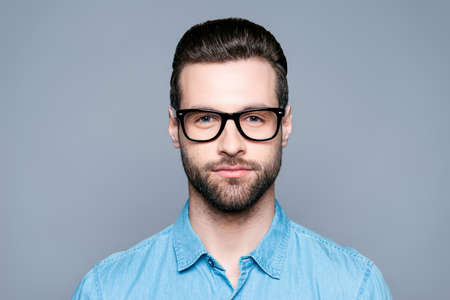 Portrait of handsome young bearded man in glasses on gray background Foto de archivo
