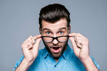 Wow! Surprised young man with opened mouth touching glasses Stock Photo